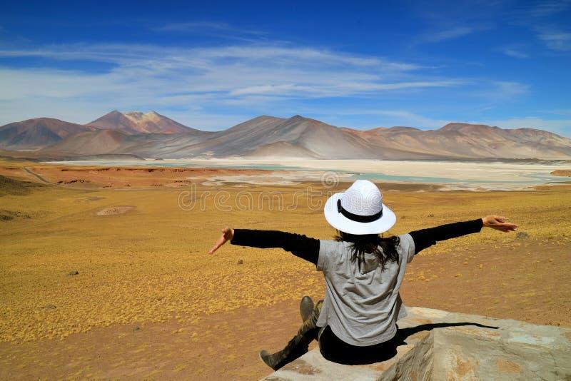 Femme soulevant ses bras devant la vue impressionnante des lacs de sel de Salar de Talar et de la montagne de Cerro Medano, Chili photos libres de droits