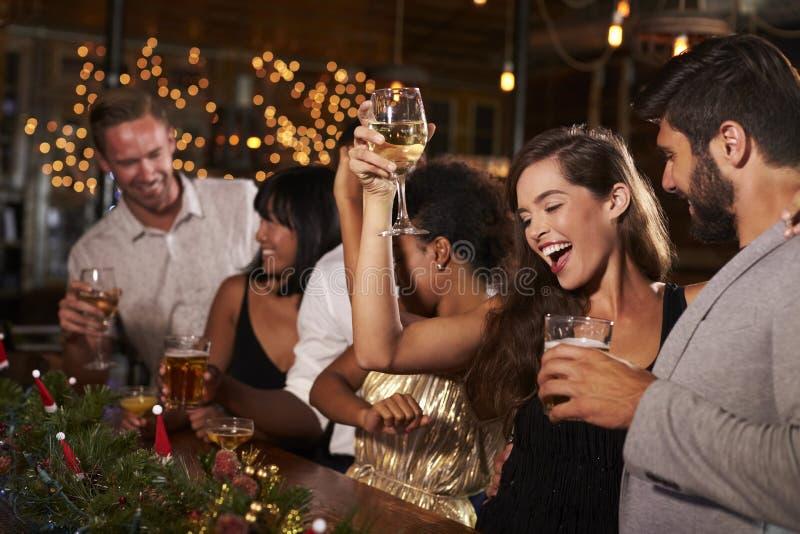 Femme soulevant un verre à une fête de Noël dans une barre image libre de droits