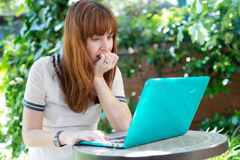 Femme soumise à une contrainte avec l'ordinateur dans le jardin photo stock
