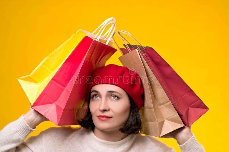Femme soumise à une contrainte fatiguée des achats Jeune femme dans le béret parmi des sacs à provisions Ventes saisonnières, con photos libres de droits
