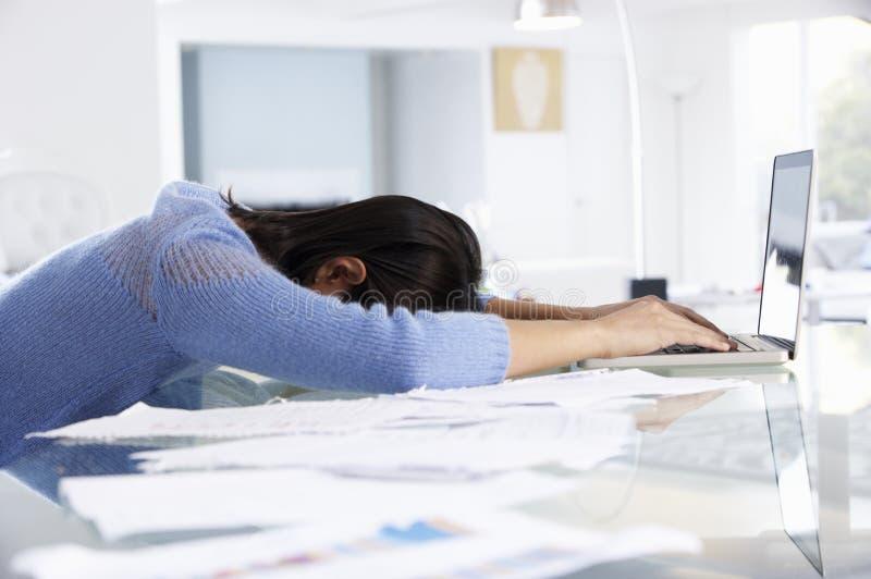 Femme soumise à une contrainte travaillant à l'ordinateur portable dans le siège social photos stock
