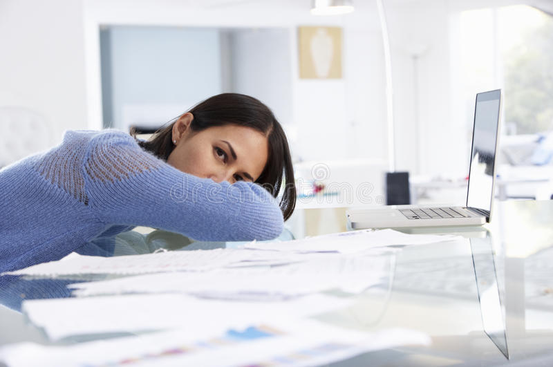 Femme soumise à une contrainte travaillant à l'ordinateur portable dans le siège social photographie stock