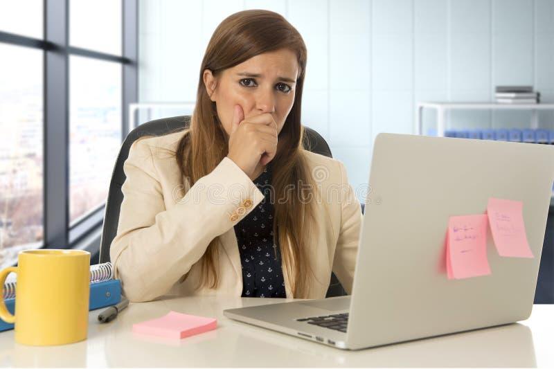 Femme soumise à une contrainte travaillant avec l'ordinateur portable sur le bureau dans surchargé images stock