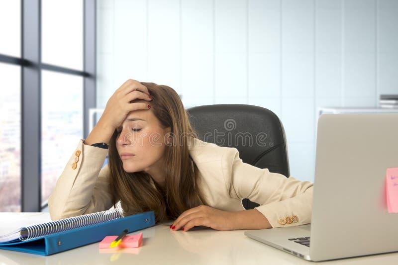 Femme soumise à une contrainte travaillant avec l'ordinateur portable sur le bureau dans surchargé photographie stock libre de droits