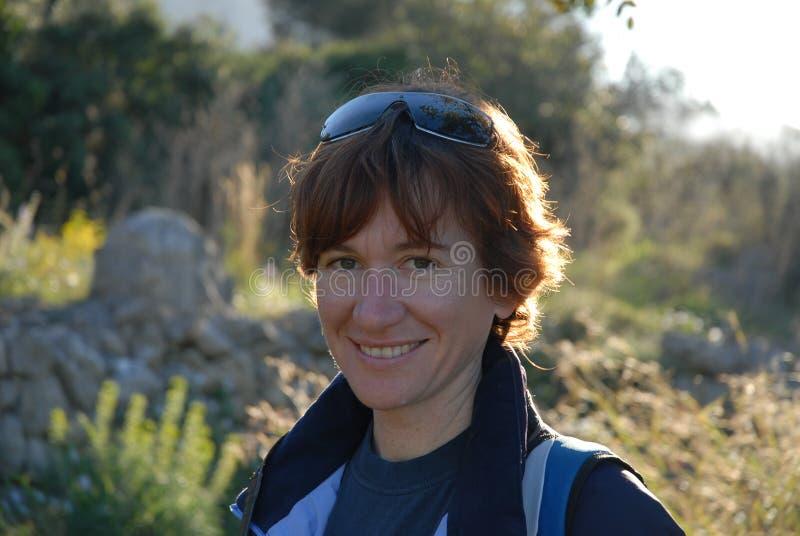 Femme souriant à la caméra, portrait dehors image stock