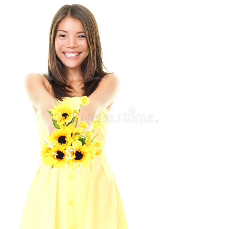 Femme souriant affichant des fleurs photos stock