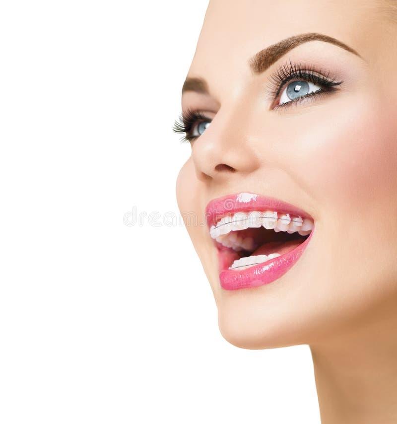 Femme souriant avec les accolades en céramique sur des dents image stock