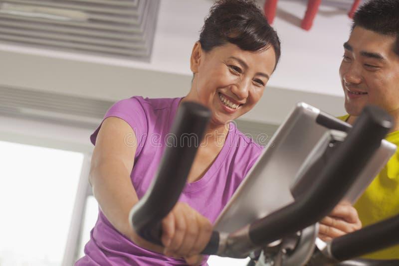 Femme souriant et s'exerçant sur le vélo d'exercice avec son entraîneur photographie stock libre de droits