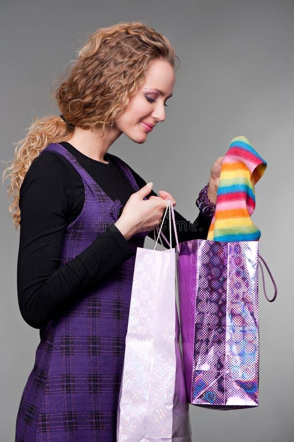 Femme souriant regardant ses achats photographie stock libre de droits