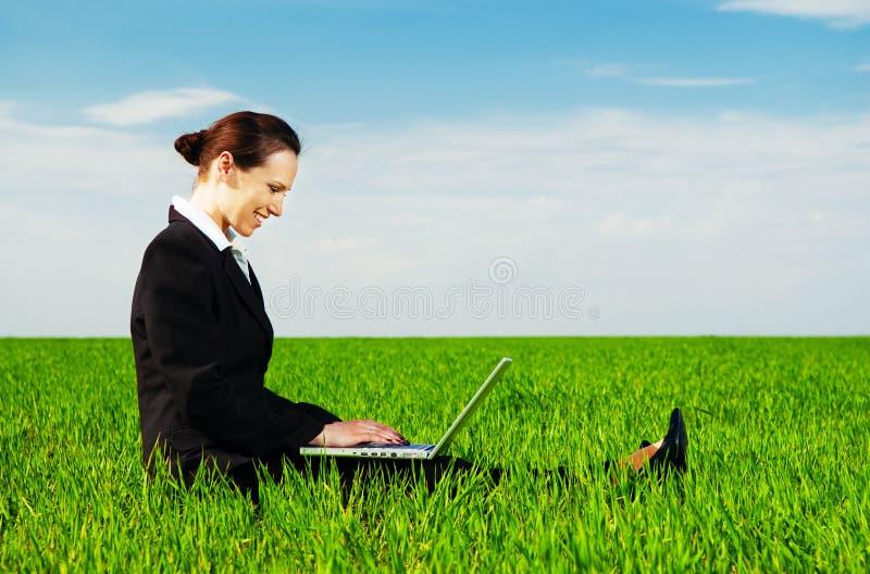 Femme souriant se reposant avec l'ordinateur portatif photo libre de droits