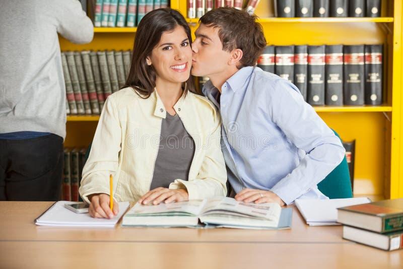 Femme souriant tandis qu'homme embrassant dans la bibliothèque photographie stock libre de droits