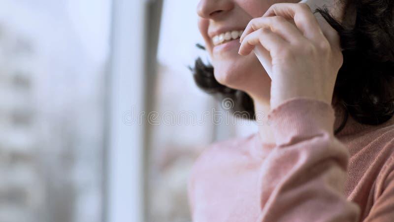 Femme souriant tout en ayant la conversation au-dessus du téléphone portable, fenêtre au fond photographie stock libre de droits