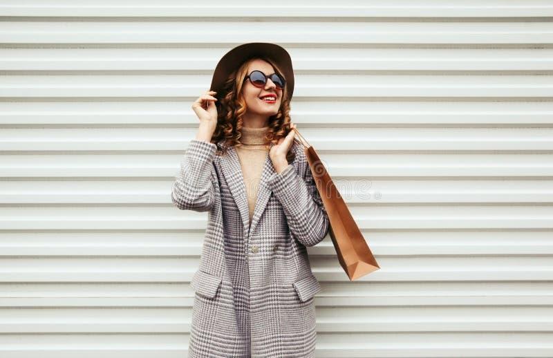 Femme souriante élégante avec son sac à provisions regardant la rue de la ville sur un mur blanc photo libre de droits