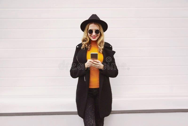 Femme souriante élégante regardant le téléphone portant une veste de manteau noire, un chapeau rond, des lunettes de soleil en vi image stock