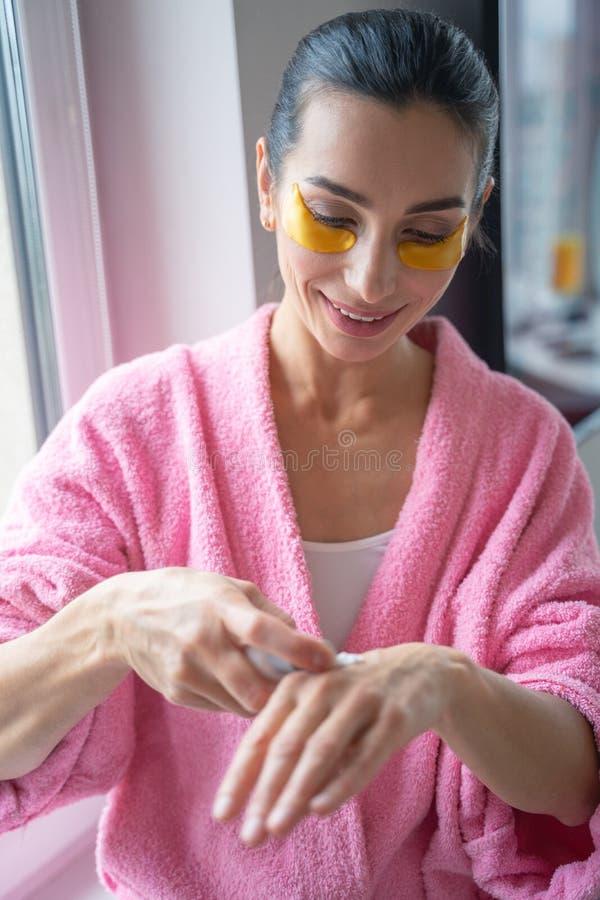 Femme souriante appliquant une nouvelle photo de bouillon de lotion photos stock