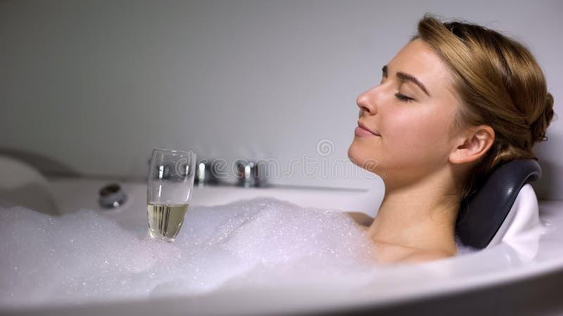 Femme souriante buvant du champagne dans son bain avec des bulles de mousse, le soir se détendre image libre de droits