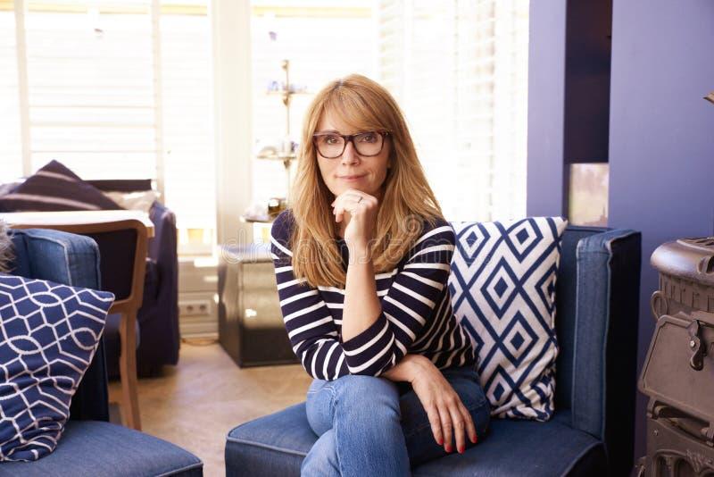 Femme souriante et confiante se reposant sur un canapé à la maison photo libre de droits