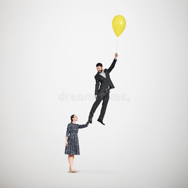 Femme souriante tenant l'homme de vol image stock