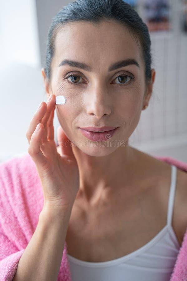Femme souriante utilisant une belle photo de bouillon de crème solaire photos libres de droits