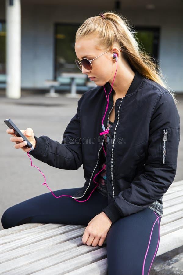 Femme sportive écoutant la musique tout en se reposant sur le banc photo stock