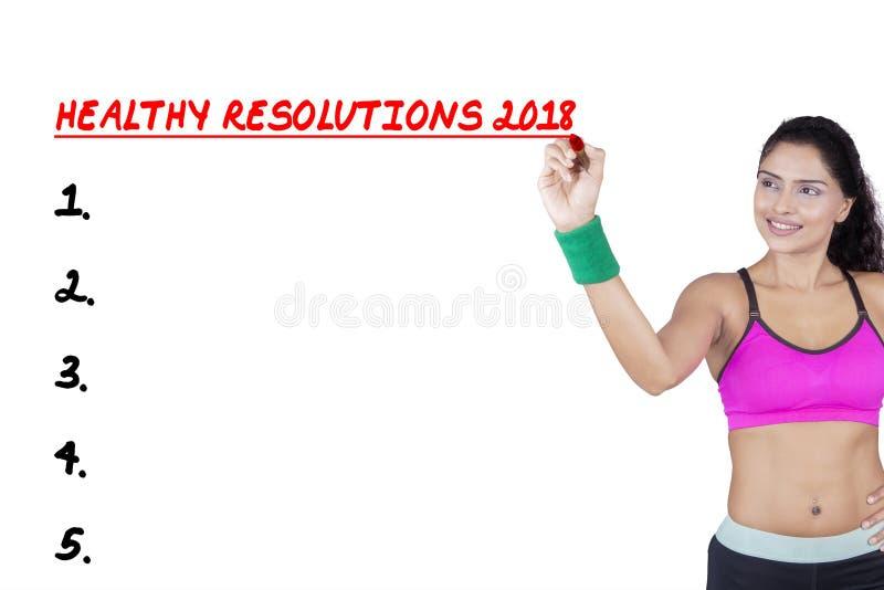 Femme sportive écrivant des résolutions saines pour 2018 photo stock