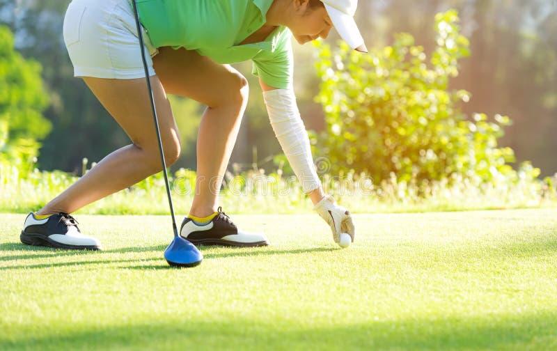 Femme sportive asiatique de main mettant la boule de golf sur la pièce en t avec le club dans g photographie stock