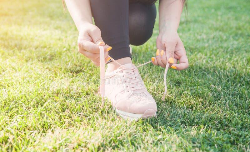 Femme sportive attachant des dentelles des chaussures de course avant de former dehors photographie stock libre de droits