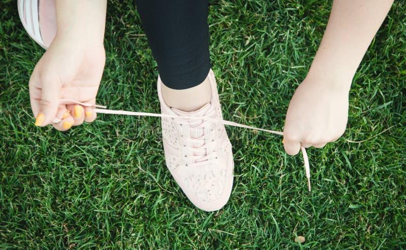 Femme sportive attachant des dentelles des chaussures de course avant de former dehors image stock
