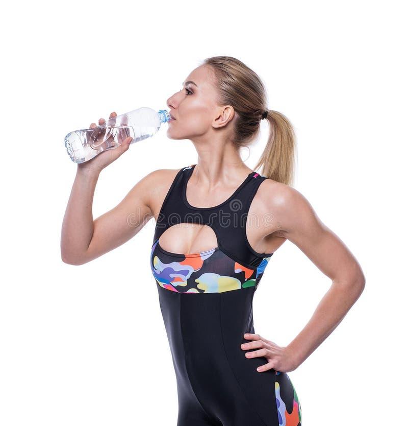 Femme sportive attirante après séance d'entraînement avec la bouteille de l'eau d'isolement au-dessus du fond blanc La fille en b photographie stock