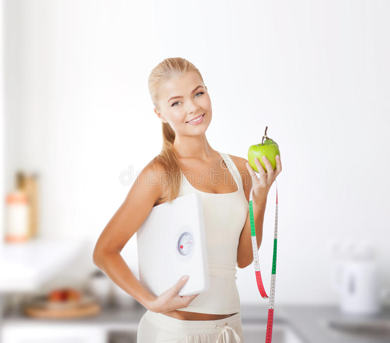 Femme sportive avec l'échelle, la pomme et la bande de mesure images libres de droits