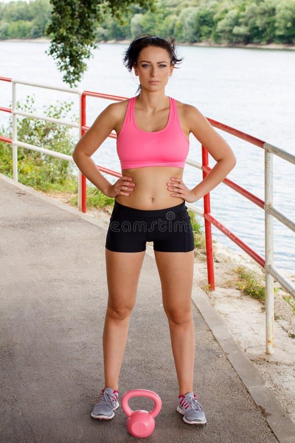 Femme sportive avec le kettlebell rose photos stock