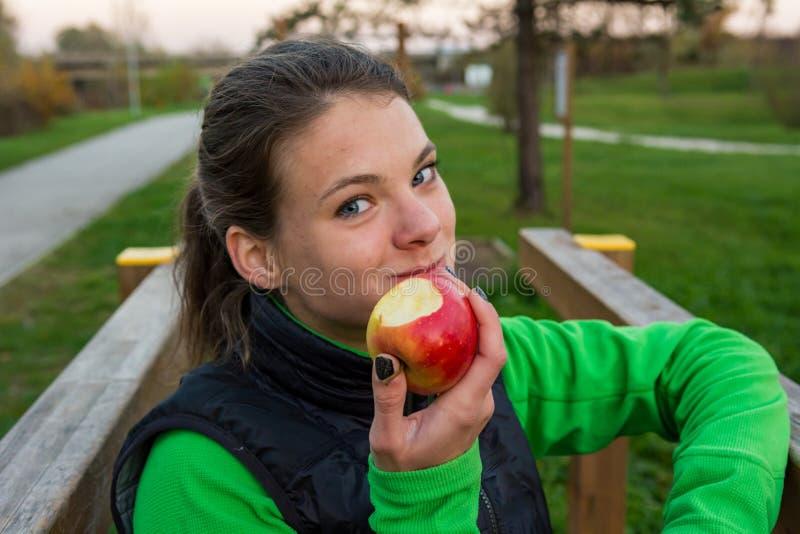 Femme sportive ayant un casse-croûte sain de fruit pendant l'exercice extérieur photographie stock libre de droits