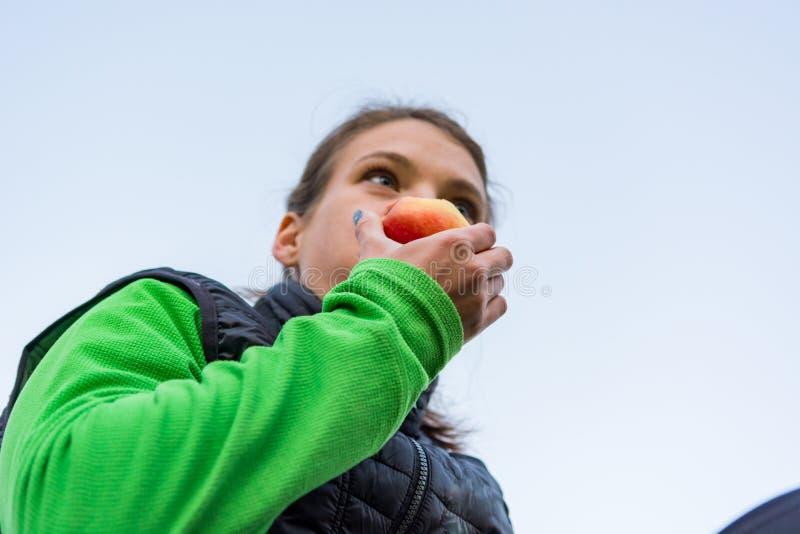Femme sportive ayant un casse-croûte sain de fruit pendant l'exercice extérieur image stock