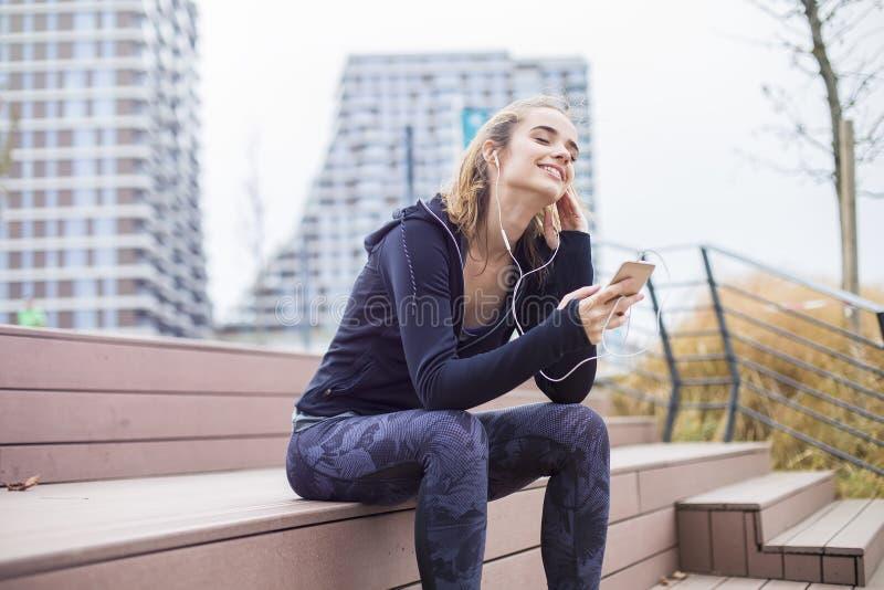 Femme sportive convenable de jeunes se reposant et écouter musique au téléphone portable photo stock