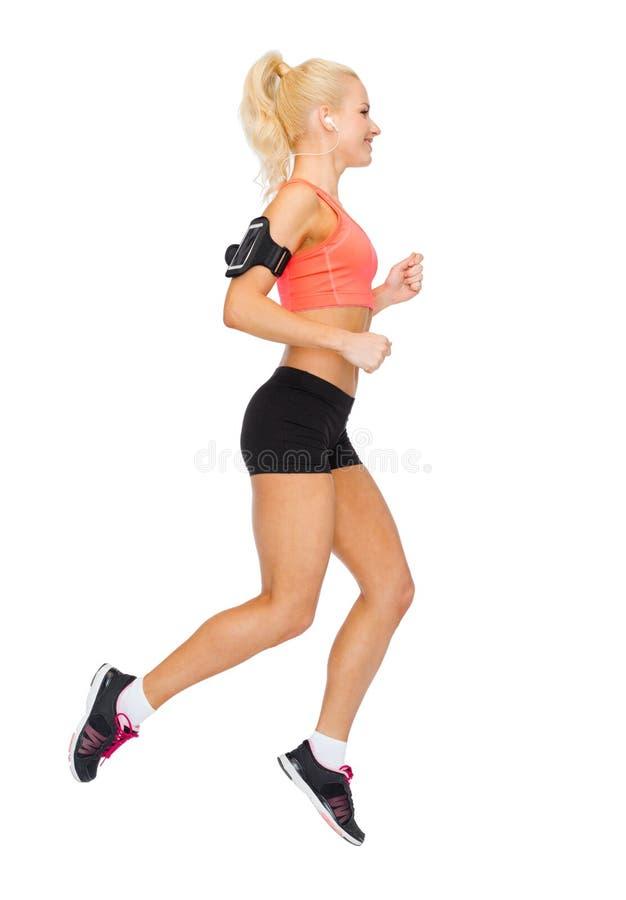 Femme sportive courant avec le smartphone et les écouteurs image libre de droits
