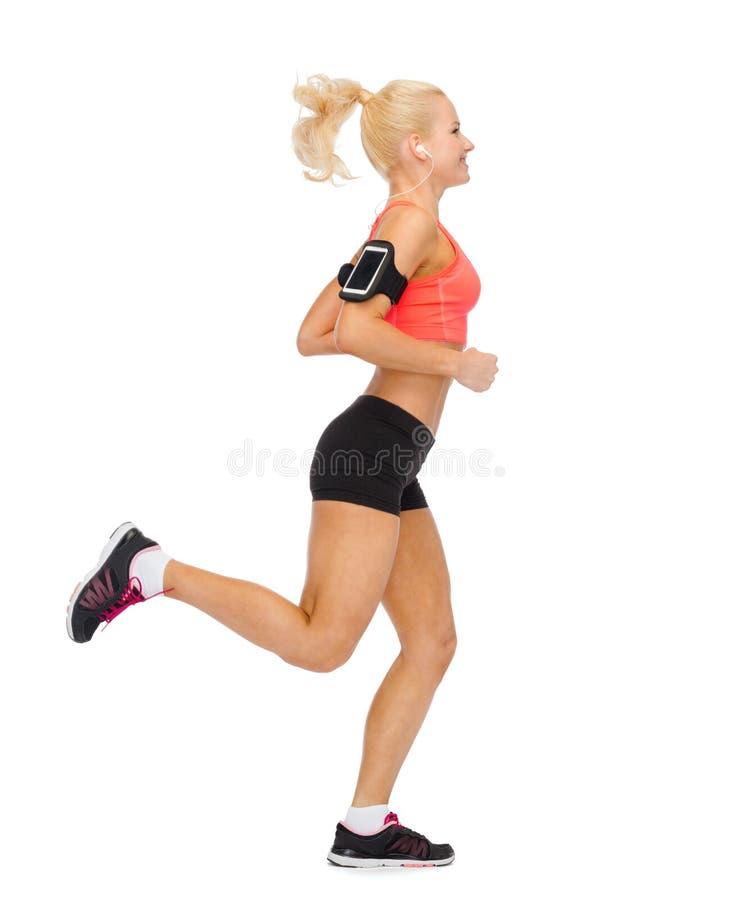 Femme sportive courant avec le smartphone et les écouteurs photographie stock