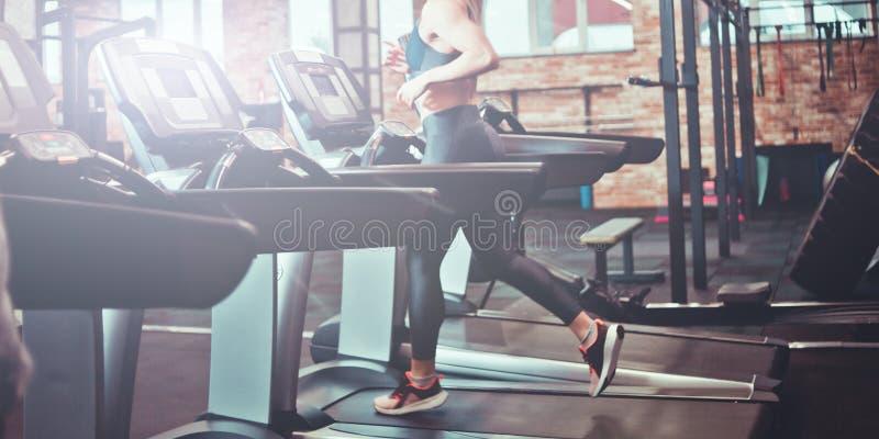 Femme sportive courant sur un tapis roulant dans le gymnase photo stock