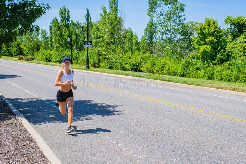 Femme sportive dans le fonctionnement de traînée de vêtements de sport sur la route La fille d'athlète pulse en parc images libres de droits