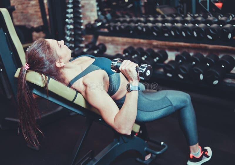 Femme sportive dans les vêtements de sport faisant une presse d'haltère sur le banc incliné au gymnase Vue de c?t? images stock