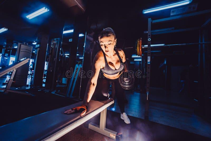 Femme sportive de bodybuilder avec des haltères belle fille blonde avec des muscles Gymnastique photos stock
