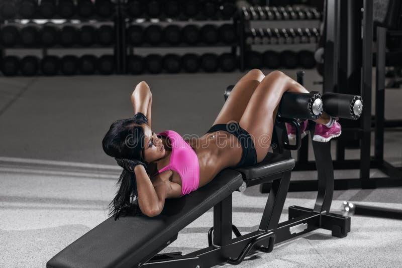 Femme sportive de brune faisant quelques craquements dans un banc au gymnase image libre de droits