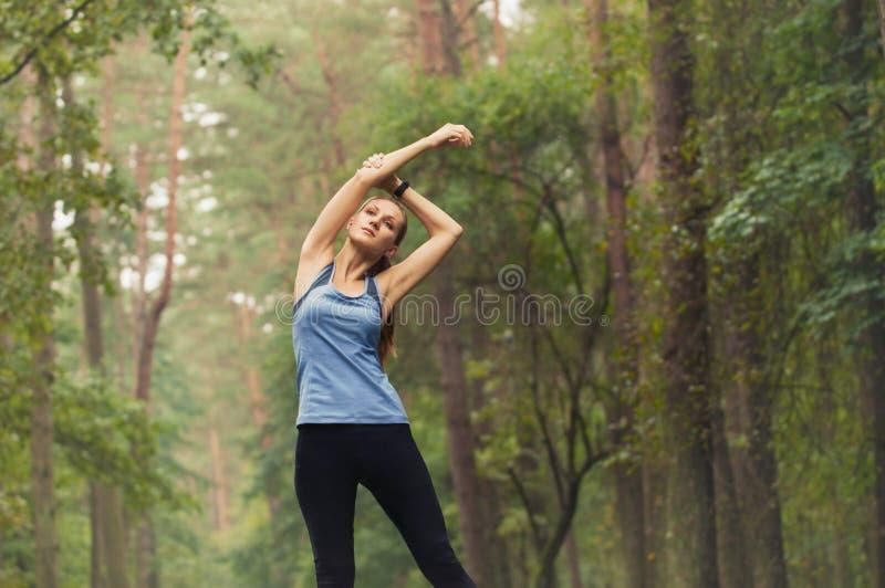 Femme sportive de forme physique saine de mode de vie s'étirant avant course dedans image libre de droits