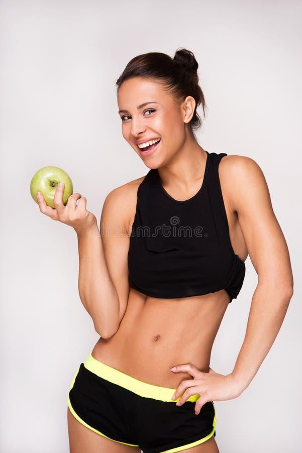 Femme sportive de métis avec une pomme images stock
