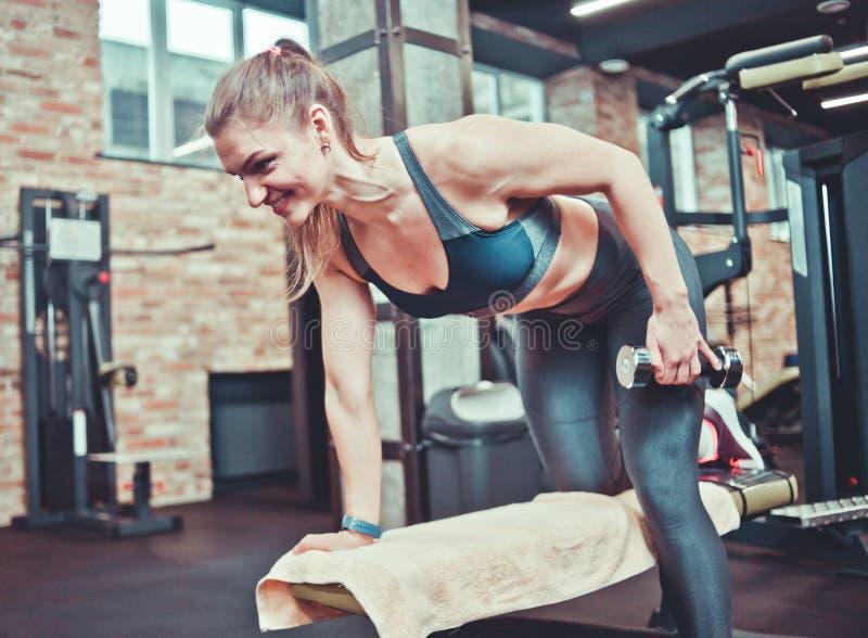 Femme sportive de Smilling tirant l'haltère sur un banc de forme physique photo stock