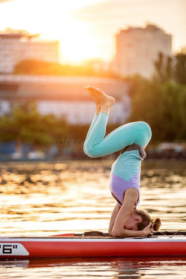 Femme sportive en position de yoga sur le paddleboard, faisant le yoga sur le panneau de petite gorgée, l'exercice pour la flexib photos stock
