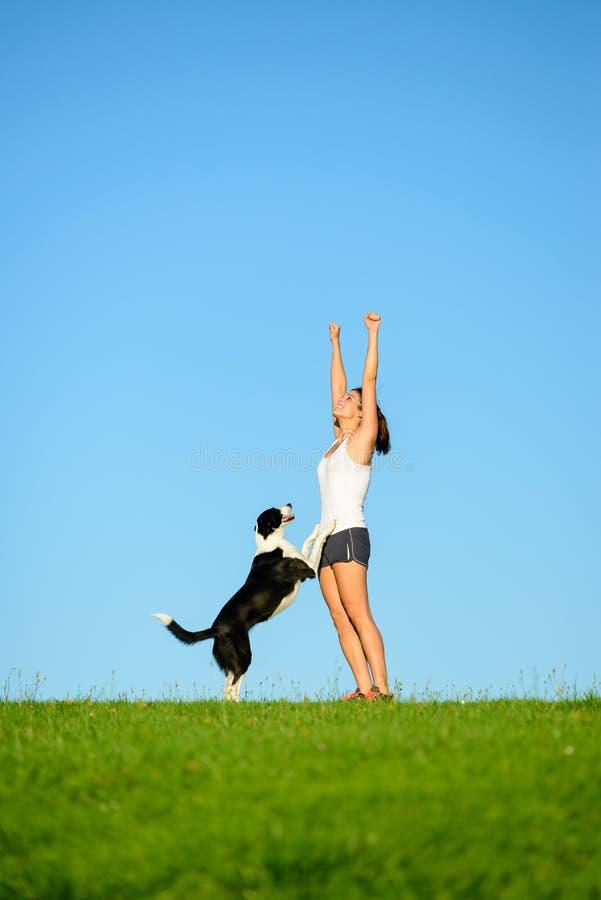 Femme sportive et chien célébrant le succès de séance d'entraînement photo libre de droits