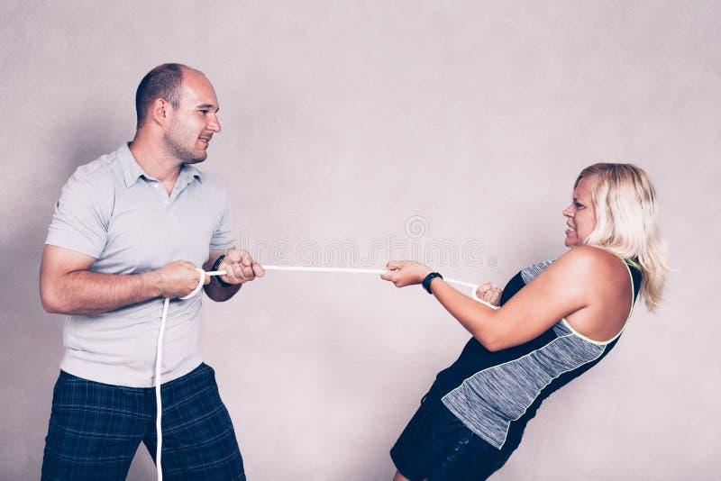 Femme sportive et homme déterminés tirant une corde photo libre de droits