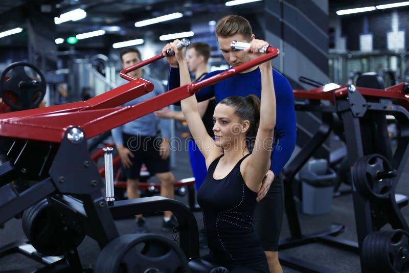Femme sportive faisant des exercices sous la surveillance de son entraîneur personnel dans le gymnase photographie stock