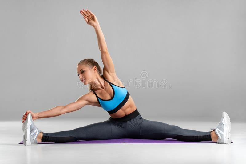 Femme sportive faisant la ficelle et étirant l'exercice, d'isolement sur le fond gris Belle fille faisant l'exercice de yoga ou d photos stock