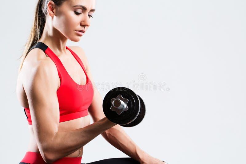 Femme sportive faisant la séance d'entraînement de forme physique avec des haltères sur le fond gris photos libres de droits